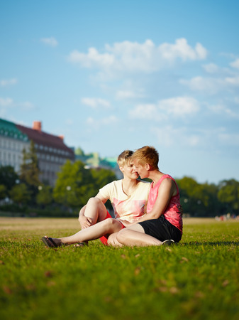 housemate: Two women embracing in the park in the afternoon sunlight, city park