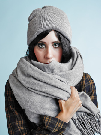 Close up portrait of beautiful young woman wearing a scarf and a woolly hat - studio shot photo