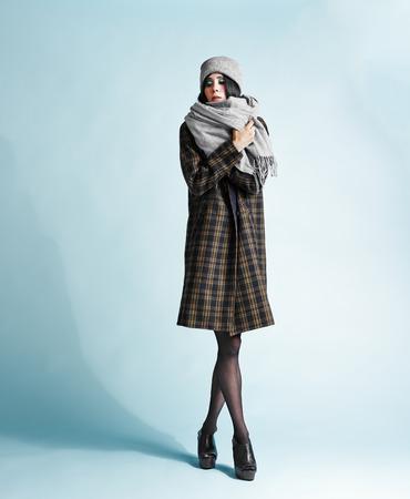 Full length portrait of beautiful young woman wearing an overcoat - studio shot photo