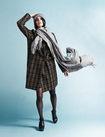 Full length portrait of beautiful young woman wearing an overcoat - studio shot