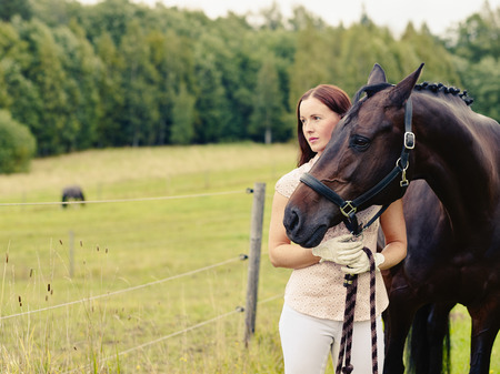 Attractive woman and horse in the field, cross processed image photo