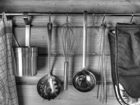 rustproof: The kitchenware hanging on the wall, black and white image Stock Photo