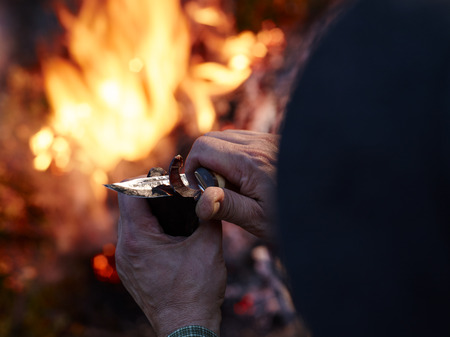 whittle: A man cuts a dried reindeer meat with a knife, camp fire on the background Stock Photo
