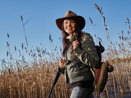 decoy: Waterfowl hunting, smiling female hunter carry a shotgun and a decoys, reeds and blue sky on background