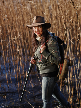 decoy: Waterfowl hunting, smiling female hunter carry a shotgun and a decoys, shore and reeds on background