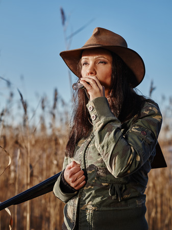 Waterfowl hunting, the female hunter carry a shotgun and she use a duck call, blue sky and reeds on background Standard-Bild