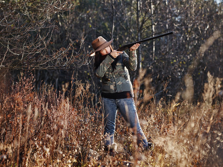 Waterfowl hunting, the female hunter use the shotgun, autumnal bushes on background Stok Fotoğraf