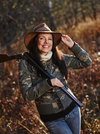 waterfowl: Waterfowl hunting, the female hunter carry a shotgun, autumnal bushes on background