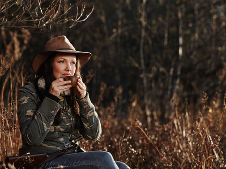 duck hunting: Waterfowl hunting, the female hunter having a coffee break, autumnal bushes on background
