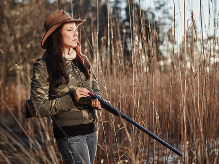 waterfowl: Waterfowl hunting, the female hunter loading the side by side shotgun, shore and reeds on background