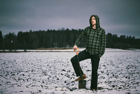 cross processed: Handsome young man and shovel, snowy plowed field - cross processed image Stock Photo