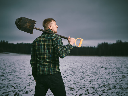 cross processed: Handsome young man and shovel, snowy plowed field  - cross processed image