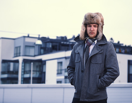 A man and wearing a fur hat and warm overcoat, apartment buildings