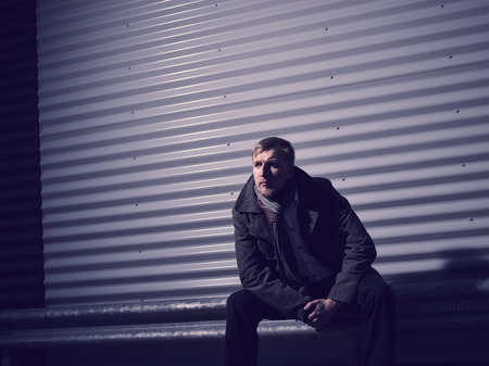 cross processed: Fashionable young man wearing a warm overcoat, corrugated iron wall on background - cross processed image
