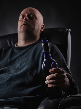 inebriated: Middle aged man sleeps on an armchair and he holding a wine bottle, vertical format Stock Photo
