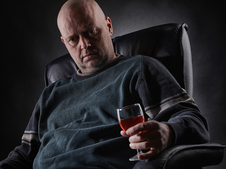 inebriated: Middle aged depressed man sits on an armchair and he holding a wine glass Stock Photo