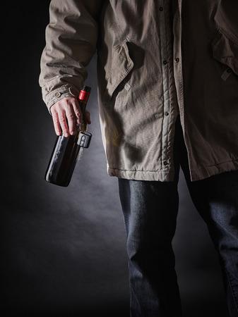 inebriated: Drunken driver holds a wine bottle and car keys on hand, vertical format