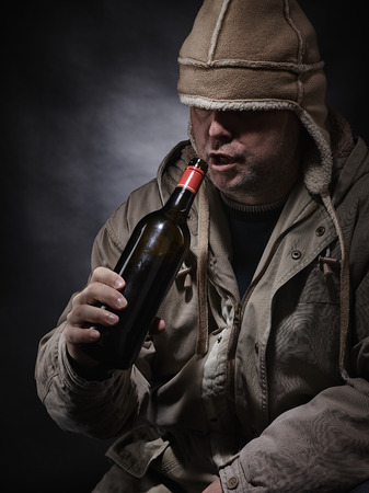 inebriated: Middle aged alcoholic and wine bottle, he wearing winter clothings - vertical format