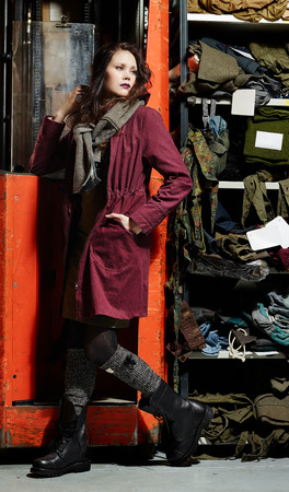 lean machine: Fashionable girl standing front of the working machine - warehouse theme and vertical full length image Stock Photo