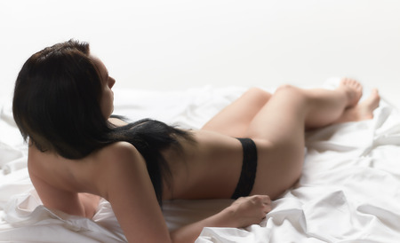 silky lingerie: Attractive seminude woman wearing lingerie and she lying on the white bed sheets