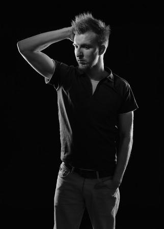 beau jeune homme: Expressive beau jeune homme - tourn� en studio, l'image en noir et blanc, fond noir