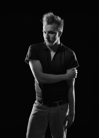 handsome young man: Expressive handsome young man - studio shot, black and white image, black background