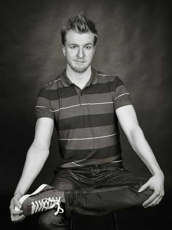 handsome young man: Expressive handsome young man sits in the studio - black and white image, dark background