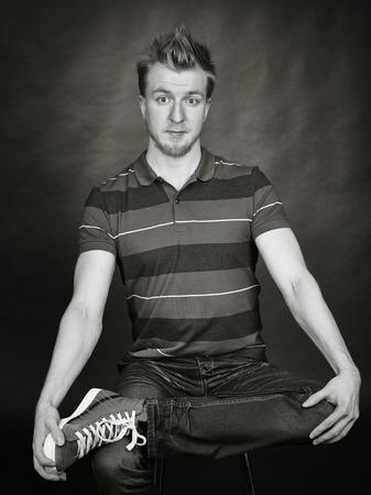 beau jeune homme: Expressive beau jeune homme assis dans le studio - image en noir et blanc, fond sombre