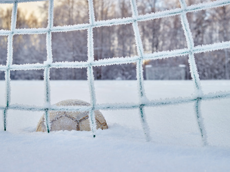 Snowy soccer field in December, frost and cold weather