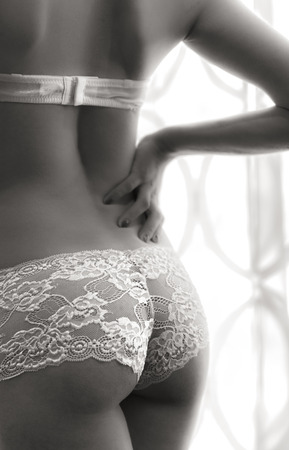 nude bride: Close up, attractive young woman wearing lingerie and she stands front of the window - black and white image