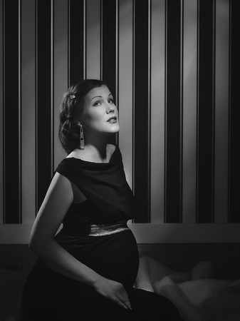 black and white, a beautiful pregnant woman - minimal lighting and strong contrast photo