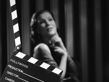 action movie: black and white, a beautiful acting woman and a clapboard - minimal lighting and strong contrast