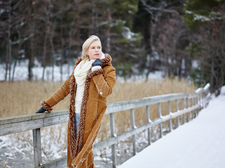 winter fashion: Fashionable mature adult woman wearing winter clothes and she standing next to the fence - rural scene