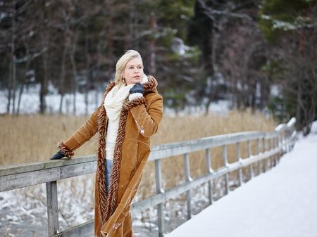 sueter: Mujer de moda adulto maduro vistiendo ropa de invierno y ella de pie junto a la valla - escena rural Foto de archivo