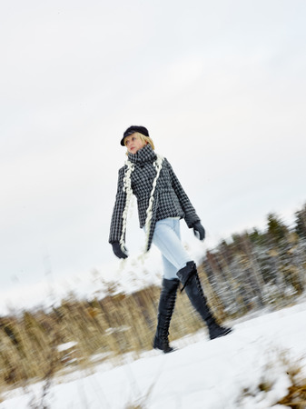 blurring: Fashionable mature adult woman wearing winter clothes, rural scene - movement, intentional blurring Stock Photo