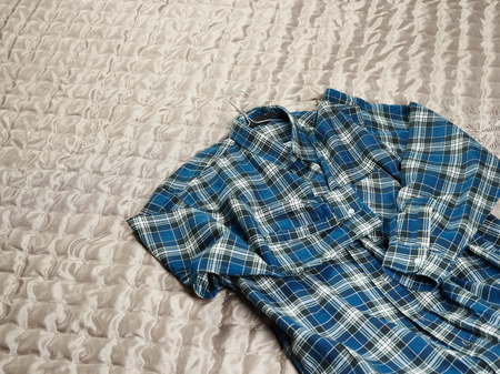 counterpane: Mens casual checkered shirt on the bed Stock Photo
