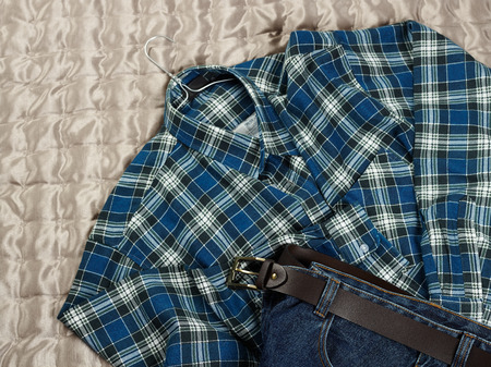 counterpane: Mens casual checkered shirt and jeans on the bed