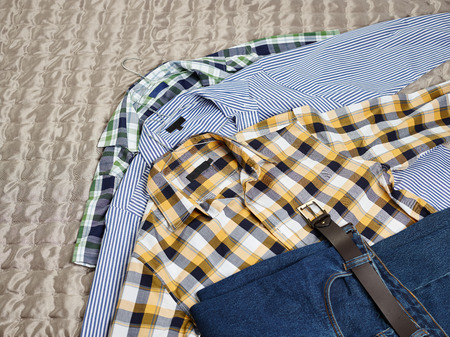 counterpane: Mens casual patterned shirts and jeans on the bed Stock Photo
