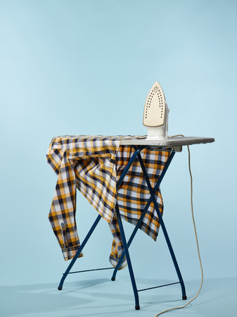 electric iron: A iron and checkered shirt on the ironing board, light blue background Stock Photo