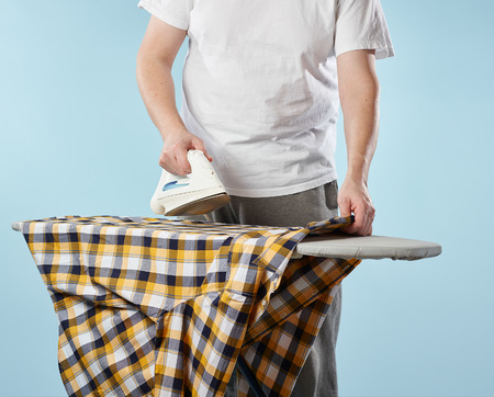 ironing board: A man, a iron and checkered shirt on the ironing board, light blue background Stock Photo