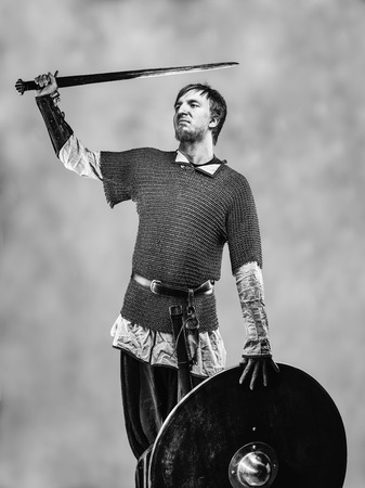 the victorious: Victorious medieval knight armor with a sword and shield, black and white image