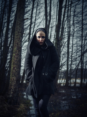 cross processed: Fashion woman wearing a winter coat and she pose in a gloomy forest, cold rainy weather, cross processed full length image