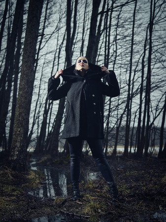 cross processed: Fashion woman wearing a winter coat and she standing in a gloomy forest, cold rainy weather, cross processed full length image Stock Photo