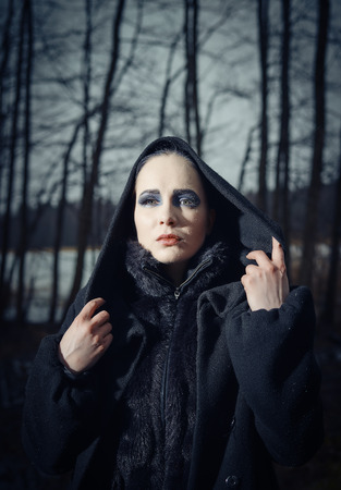 cross processed: Fashion woman wearing a winter coat and she pose in a gloomy forest, cold rainy weather, cross processed image, close-up