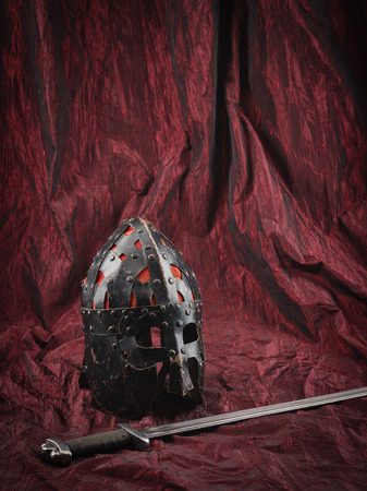 medieval blacksmith: Medieval helmet and sword, red canvas background