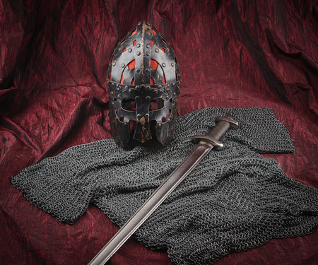 ancient blacksmith: Medieval armour, helmet and sword, red canvas background Stock Photo