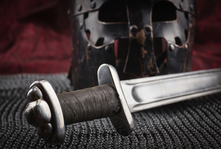 Medieval armour, helmet and sword, red canvas background Standard-Bild