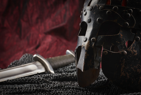 Medieval armour, helmet and sword, red canvas background 版權商用圖片
