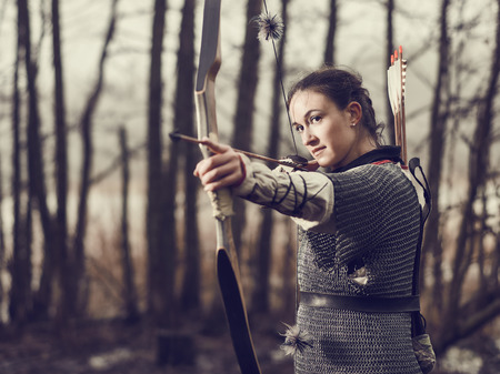 Medieval archer woman, she wearing a chainmail and use a bow and arrow, gloomy forest, cross-processed image. 版權商用圖片