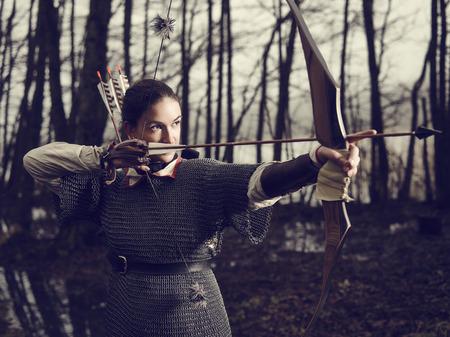 medievales: Mujer arquero medieval, ella llevaba una cota de malla y utilizar un arco y una flecha, bosque sombr�o, imagen entre procesados.